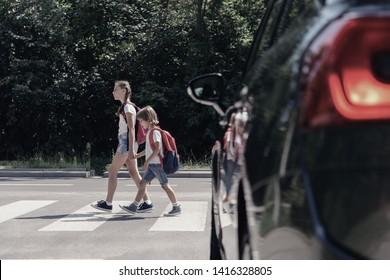 Low angle on car in front of children with backpacks walking through crosswalk to the school