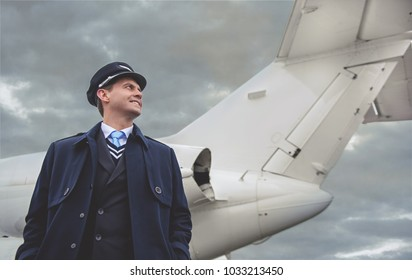 Low angle outgoing male pilot situating near tail of plane. Occupation concept