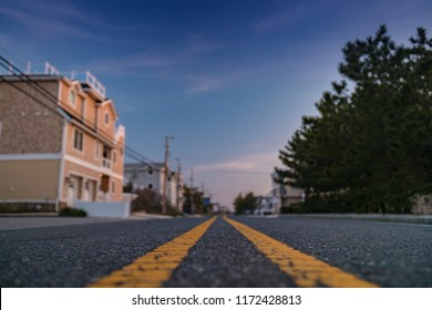 Low angle paved road view with houses in the distance