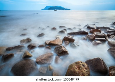 low angle of pebble in surf, seascape of long time exposure.