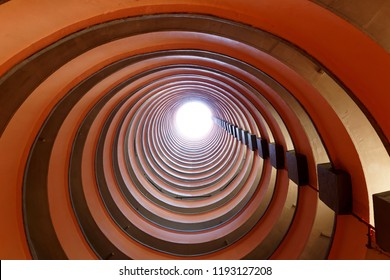 Low angle perspective from the circular atrium of a multistorey public housing estate in Hong Kong with sunlight cast from top of the tower & multilayers of corridors making a unique eccentric pattern