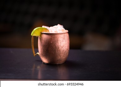 Low angle perspective close up of copper mug with bronze handle filled with acidic Moscow mule alcoholic beverage overflowing with ice cubes and sour lime slice garnish isolated on counter top bar