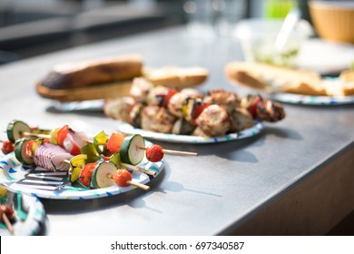 Low angle perspective on decorative paper plate stacked with homemade grilled vegetarian vegetable skewers beside charr roasted chicken kabab on buffet table with blurry barbecue cookout background