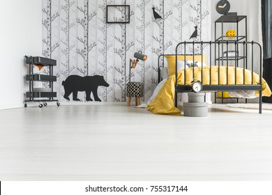Low angle photo of kid's room with handmade lamp and yellow bedding on metal bed