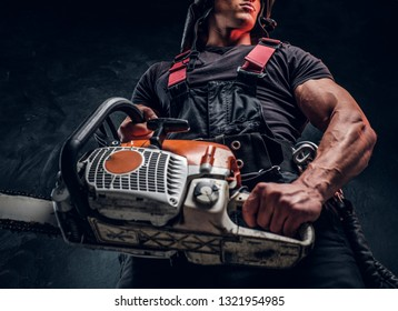 Low angle photo of a logger with a chainsaw in a dark studio