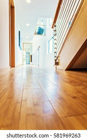 Low angle photo of a modern home interior hallway with hardwood floors; shallow depth of focus.