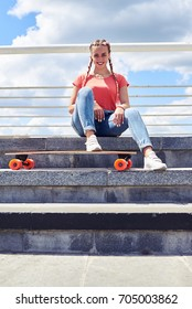 Low angle of pleased female having rest on stairs after riding skateboard with copy space