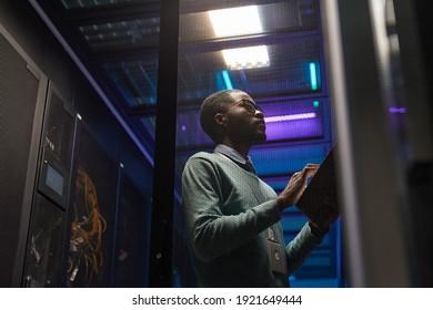 Low-angle-Portrait des afroamerikanischen Dateningenieurs, der mit Supercomputer im Serverraum arbeitet, der durch blaues Licht beleuchtet ist, Kopienraum