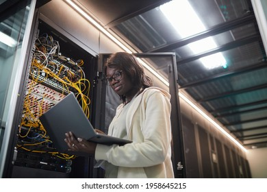 Low angle portrait of African-American female network engineer standing by server cabinet and holding laptop while working with supercomputer in data center, copy space