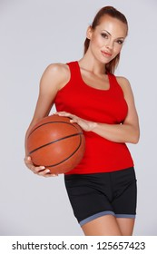 Low angle portrait of an attractive woman with a basketball in her hands posing in shorts against a grey studio background