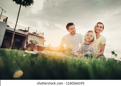 Low angle portrait of beaming bearded man talking with cheerful wife. She holding outgoing small girl. Basket with vegetables locating near them. Pleased couple with beaming kid during picnic concept