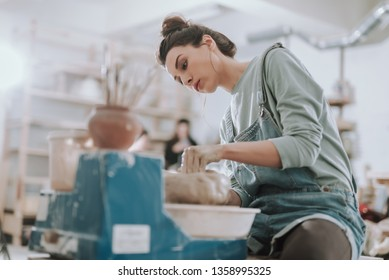 Low angle portrait of craftswoman in denim overalls making clay pot in pottery workshop. Copy space in left side