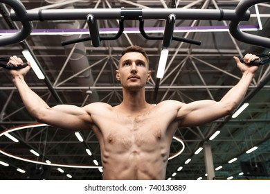 Low angle portrait of determined young man with bare chest pumping arm muscles working out on machines in gym