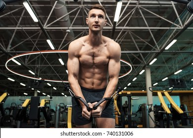 Low angle portrait of determined young man with bare chest pumping muscles working out on machines in gym  in dramatic light