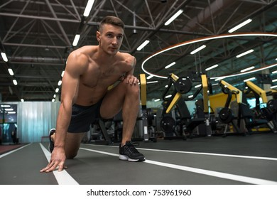 Low angle portrait of determined young runner with bare chest ready to start on track in modern gym
