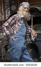 Low angle portrait of an elderly man with a beard and coveralls, standing in a garage in front of a vehicle he is restoring.
