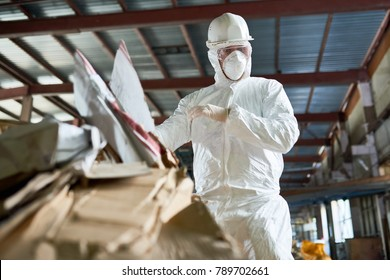 Low angle portrait of factory worker wearing biohazard suit sorting reusable cardboard on waste processing plant, copy space