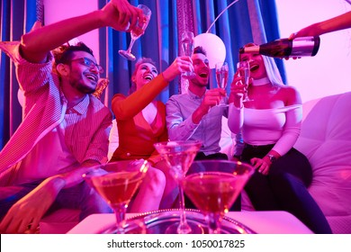 Low angle portrait of group of glamorous  people enjoying private party, sitting on sofa laughing happily while waitress pouring champagne to flute glasses