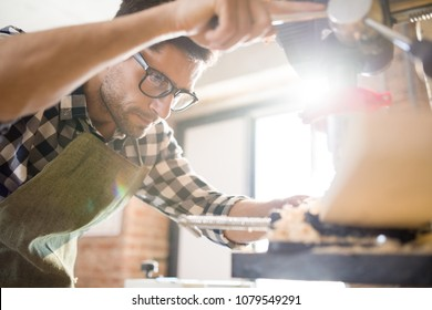 Low angle portrait of handsome modern artisan using machines while working  with wood in carpenters shop lit by sunlight, copy space