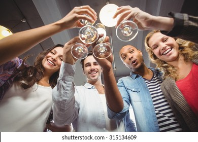 Low angle portrait of happy colleagues toasting with champagne in creative office