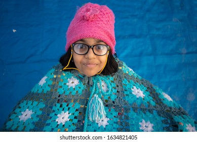 Low angle portrait of an Indian brunette baby girl with woolen clothes, cap and spectacles doing funny facial expression in a casual mood on a rooftop in winter afternoon. Indian lifestyle.