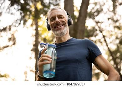Low-Winkel-Porträt von freudig gegrilltem athletischen männlichem Trinkwasser während des Trainings in sonnigen Wäldern