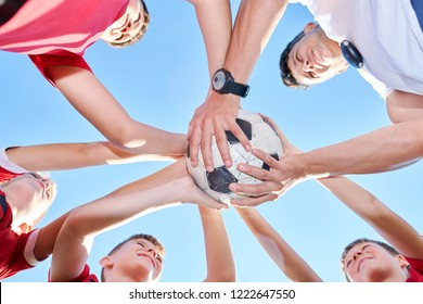 Low angle portrait of junior football team standing in circle and holding ball while huddling before match