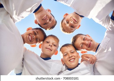 Low angle portrait of junior football team standing in circle smiling  at camera, huddling before match