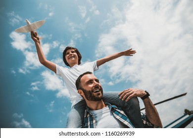 Low angle portrait of laughing bearded man and positive kid having fun with plastic toy under blue sky with white fluffy clouds