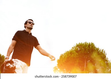 Low angle portrait of professional golf player walking to the next hole holding bag for clubs, good golf game at summer evening weekend on the course, golf player against flare sunset light