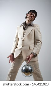 Low angle portrait of a retro man in a 1970s leisure suit and sunglasses holding a disco ball - mirror ball between his legs