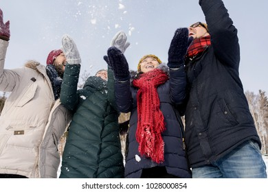 Low angle portrait of two young couples laughing happily having fun outdoors throwing snow, copy space