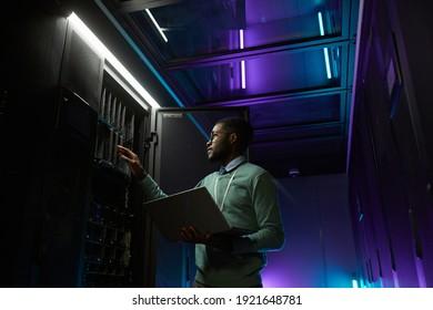 Low-angle-Porträt eines jungen afroamerikanischen Dateningenieurs, der mit einem Supercomputer im Serverraum arbeitet, der durch blaues Licht beleuchtet ist und einen Laptop hält, Kopienraum