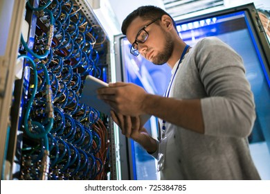 Low angle  portrait of young man using digital tablet standing by server cabinet while working with supercomputer in blue light