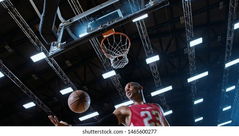 Low angle of professional basketball player in action performing slam dun in a basketball hoop on a sports arena