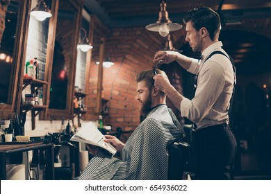 Low angle profile view of red bearded stylish barber shop client, which is getting his perfect  haircut from a classy dressed stylist, reading the magazine and waiting for result
