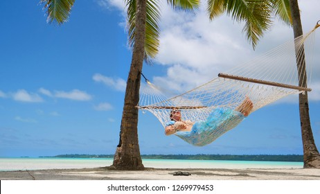 LOW ANGLE: Relaxed Caucasian woman sleeps on the tropical sandy beach in a swaying rope hammock under a tall palm tree. Young female traveler unwinds by taking a nap in a hammock right by the ocean.