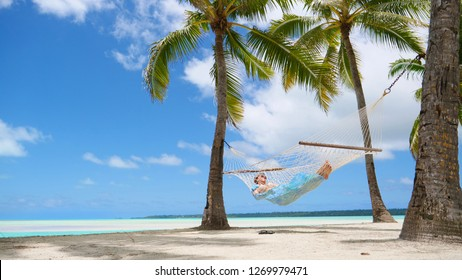 LOW ANGLE: Relaxed tourist girl sleeping in a hammock under the lush palm trees on the breathtaking sandy beach on remote paradise island in the Pacific. Young woman swaying in hammock during vacation