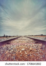 A low angle of a rural train track and a storm brewing in the north.