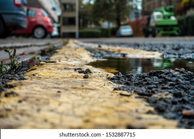 A low angle, shallow depth of field view of a puddle at the edge of a road with painted double yellow lines running through it.