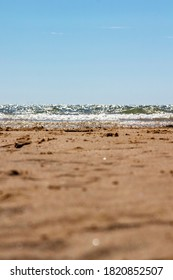 Low angle shot of the beach looking towards Frinton with shallow depth of field focus on sand. Walton on the Naze, Essex, United Kingdom