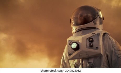 Low Angle Shot of the Brave Astronaut in the Space Suit Looking Around Alien Planet. Red and Orange Planet Similar to Mars. Advanced Technologies, Space Travel, Colonization Concept.