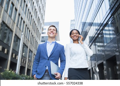 Low angle shot of business people with gadgets. Handsome business man and his beautiful female colleague walking outdoors during office break, urban scene on background