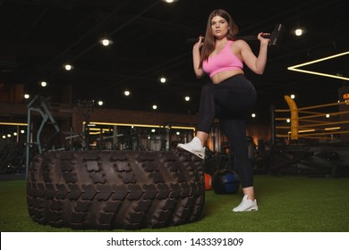 Low angle shot of a confident beautiful plus size sportswoman looking fiercely to the camera, posing with a sledgehammer near heavy wheel at the gym, copy space