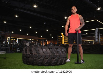 Low angle shot of a confident strong African sportsman resting after exercising with sledgehammer. Handsome male athlete relaxing after functional training session, hitting tire with a sledgehammer