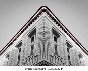 A low angle shot of the corner of an old brick building in grayscale