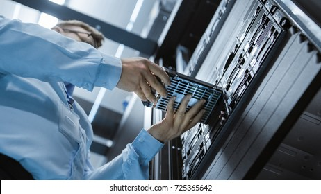 Low Angle Shot In Fully Working Data Center IT Engineer Installs Hard Drive into Server Rack. Detailed and Technically Accurate Footage.