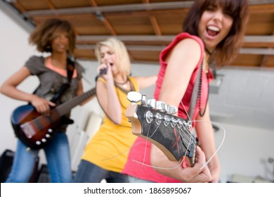 Low angle shot of a group of teenage girls standing in a garage band and singing with selective focus on guitar headstock