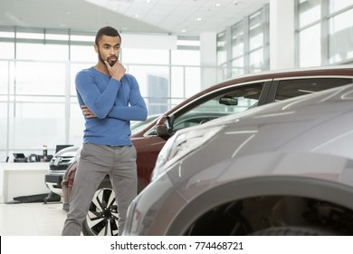 Low angle shot of a handsome African man choosing a new car at the dealership rubbing his chin thoughtfully thinking copyspace buying buyer choice decision consumerism lifestyle sale discount price