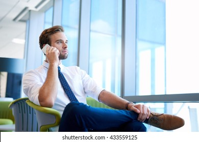 Low angle shot of a handsome young businessman in a stylish modern office space with large windows, talking on the phone and looking outside